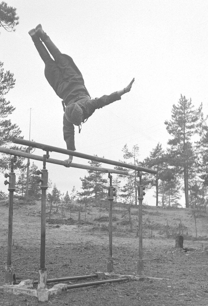 Lääkintämajuri Heikki Savolainen virittämillään nojapuilla Syvärin lohkolla 1942. Savolainen voitti 24 vuotta kestäneen olympiauransa aikana kaksi kultamitalia, yhden hopean ja kuusi pronssia ja oli voimistelun epävirallinen maailmanmestari vuodelta 1931. Hän oli syntynyt Joensuussa ja teki elämäntyönsä Kajaanin kaupunginlääkärinä. Talvisodassa hän palveli pataljoonanlääkärinä ja jatkosodassa kenttäsairaalan päällikkölääkärinä. - SA-kuva Urheilu ja sota -teoksen kannessa.